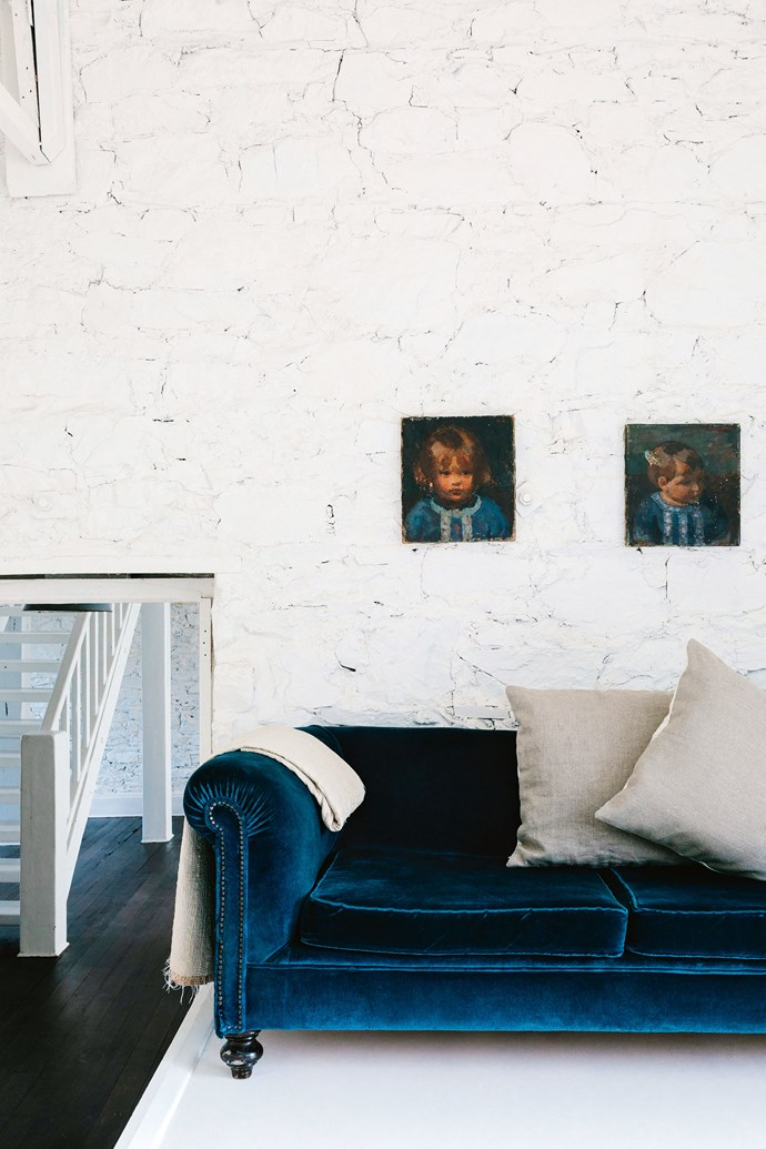 """A velvet sofa adds a soft touch to the lounge room, where the [exposed stone walls](https://www.homestolove.com.au/a-heritage-sandstone-cottage-renovation-4285