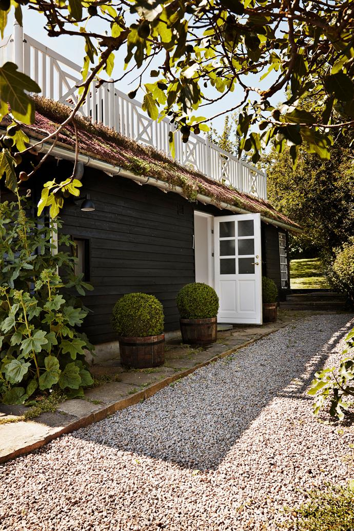 A pebble pathway leads to the side entrance. Behind the exterior's black cladding is a light-filled, comfortable family escape.