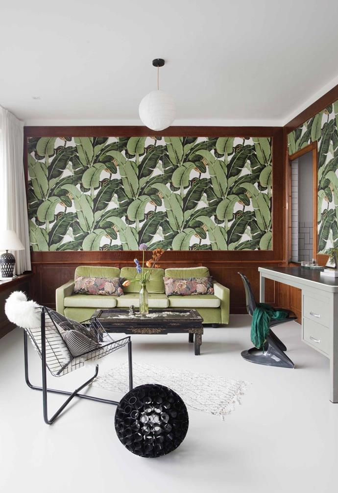 "**Master bedroom** Vinyl 'Banana Leaf' wallpaper bought online from TropicWall is a powerful backdrop and complements an Artifort sofa. ""My coffee table was part of an antique Chinese dining table, but I made the legs shorter,"" says Erika. The 'Jårpen' wire armchair was designed in 1983 by Niels Gammelgaard for [IKEA](https://www.ikea.com/