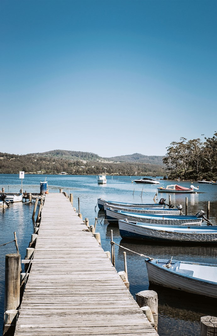 A jetty with boats for hire juts out from the boardwalk at Merimbula.