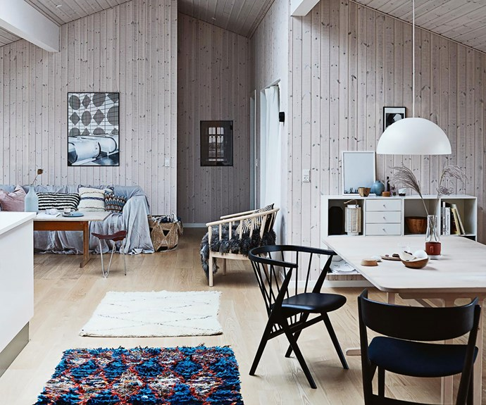 Interior of blonde timber cabin with open plan living and dining room