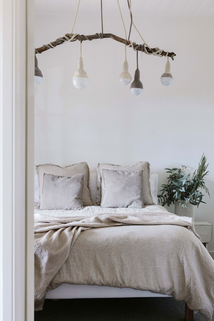 """Edwina wrapped Luna Lana lights from Stephanie Ng Design around an old branch in the bedroom. The bed linen is from [Cultiver](https://cultiver.com.au/ target=""""_blank"""" rel=""""nofollow"""")."""