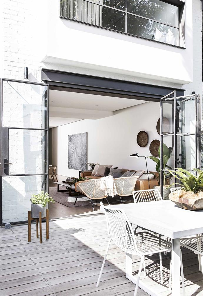 "In the kitchen, the long and deep marble-clad bench sits along the wall, with appliances hidden behind custom joinery. Steel-framed windows frame a view to a vibrant [vertical garden](https://www.homestolove.com.au/creative-and-inspiring-vertical-gardens-18432|target=""_blank""), which makes the narrow space feel more expansive.<br><br>**Outdoors** ""We wanted the outside to be an extension of the living space,"" says Ariana of the back deck. Steel-framed windows fold back to allow access to the entertaining area. Pedrali chairs from Cafe Culture + Insitu reflect the interior's clean lines."
