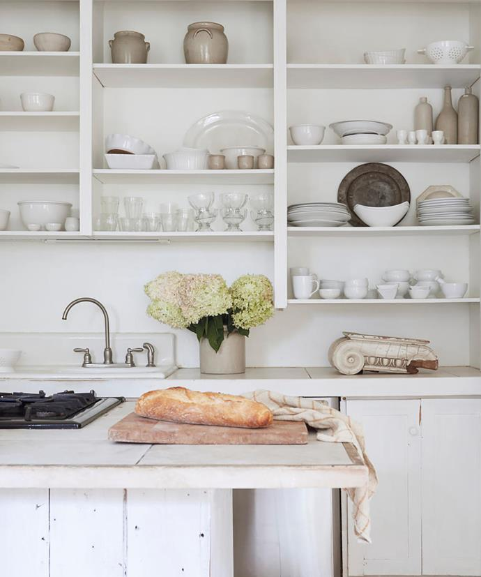 In the New England state of Vermont a country kitchen is enlivened with a jug of hydrangeas, shelves of white china and breadboards in Nora Murphy's Country House.
