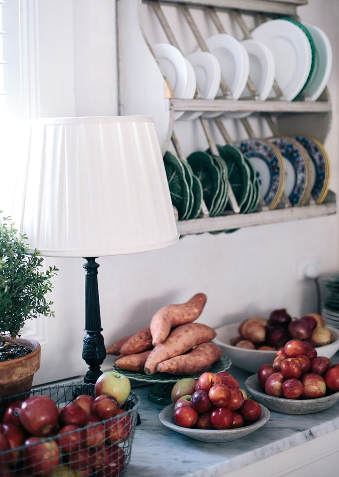 Melissa Penfold piles shiny red apples and kumera in bowls and baskets with plates lined in wall racks at her NSW southern highlands country house.