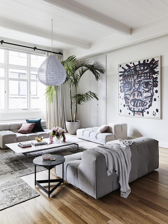"**Designate zones:** When it comes to the [layout of your living room](https://www.homestolove.com.au/15-ways-to-lay-out-your-living-room-for-comfort-and-conversation-12416|target=""_blank""), pushing all the furniture against the walls might seem like a good idea, but actually, it can make your room feel smaller. Instead, break the room into ""zones"" - here, the entertaining zone is anchored with the rug and bordered by the lounge and armchair. *Photo:* James Geer / *bauersyndication.com.au*"