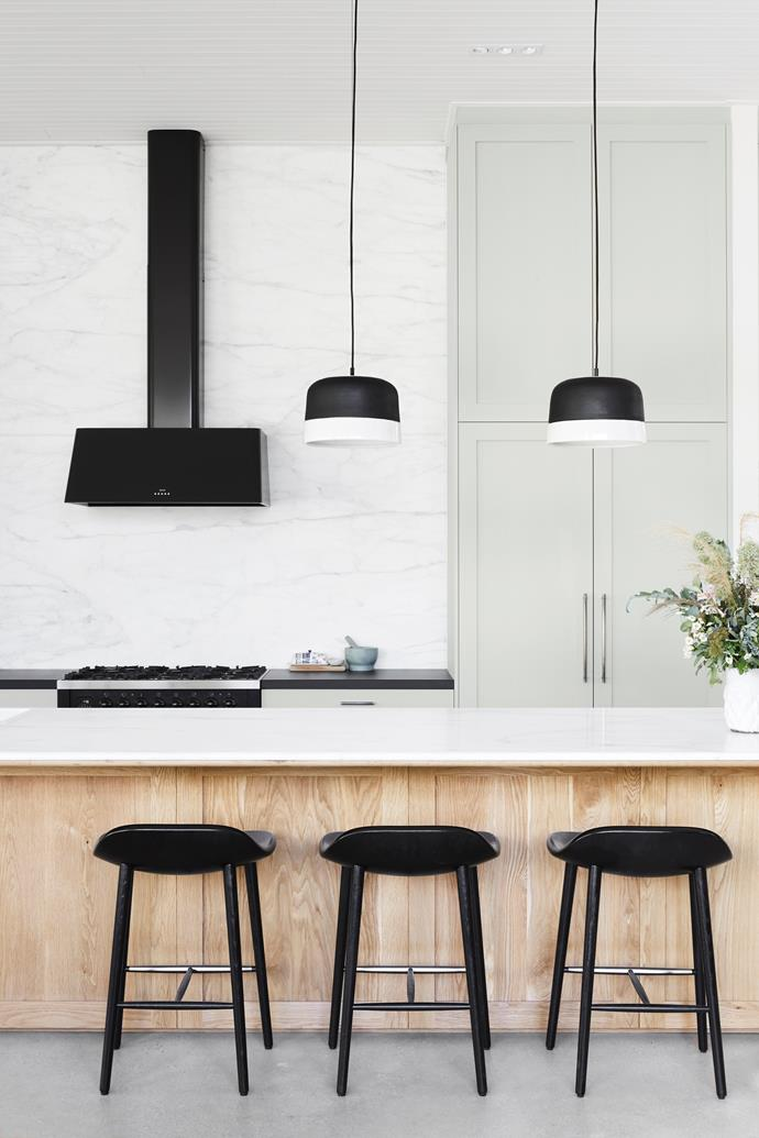 "One of the ways French-provincial style has been reimagined in contemporary homes is to strip the look right back. Where classic French style is quite ornate, these days it's all about clean lines with good quality materials. The kitchen here, created by [Enoki](https://www.homestolove.com.au/modern-beach-house-6894|target=""_blank""), features a generous marble splashback, timber panelling, and of course, a show-stopping rangehood. In this [restored homestead in South Australian wine country](https://www.homestolove.com.au/historic-homestead-restoration-south-australia-19525