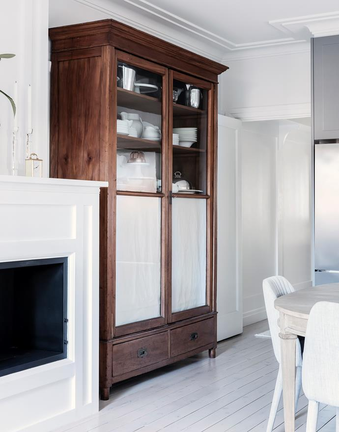 """**Styling by Natasha Levak** <p> HEIRLOOM HERO: Merisier cherrywood cabinet<p> """"A French Directoire-style cabinet made in the late 18th century was brought into this refurbished 1930s apartment for two reasons: to increase the storage capacity in the kitchen cabinetry and simply because it looks great. The cabinet houses the owners' dinnerware and stemware, and adds a rich timber tone to the otherwise white and grey interior.""""  <br></br> *French Directoire Merisier cherrywood cabinet, clients' own. Fabric (lining the doors) in Lyon glazed linen, Westbury Textiles. Vintage American bleached-maple dining table, Dirty Janes Emporium. Wall painted Murobond Paint Just White. Photograph*: Maree Homer. Paddington, NSW; [natashalevak.com](http://natashalevak.com/