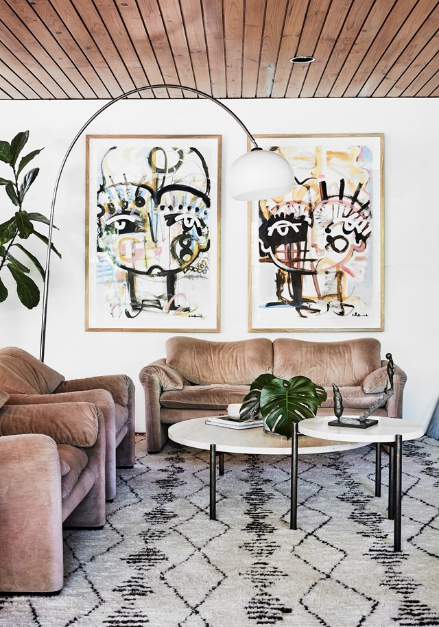 "Every artwork in [Lill Jenner's modernist home](https://www.homestolove.com.au/modernist-home-architect-peter-hall-19918|target=""_blank"") has a story, including these two paintings by Sally King Benedict. ""We commissioned Sally to do these pieces of our twins. They capture the essence of our girls perfectly!"" The sculpture by Peter Tilley on the nest coffee table was a wedding gift."