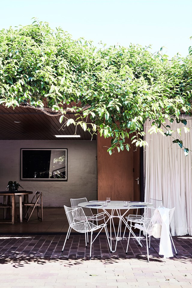 "A simple white table from Spence & Lyda and vintage chairs sit under the shade of a wisteria vine at this [modernist home in Sydney](https://www.homestolove.com.au/modernist-home-architect-peter-hall-19918|target=""_blank"")."