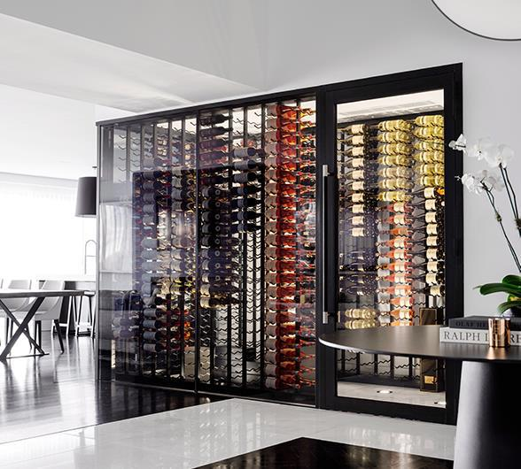 This above-ground wine cellar elevates this already luxurious Gold Coast home. Ceiling-to-floor glass doors and walls help turn this room within a room into the visual spectacle it is, and allow it to be enjoyed from both the kitchen and dining room. <br><br> Neatly storing hundreds of bottles of sparkling, white, red and dessert wines, the clever placement of the steel racks ensure bottle labels can be easily read. Talk about a dream organisation system. *Photo: Justin Alexander / Bauersyndication.com.au*