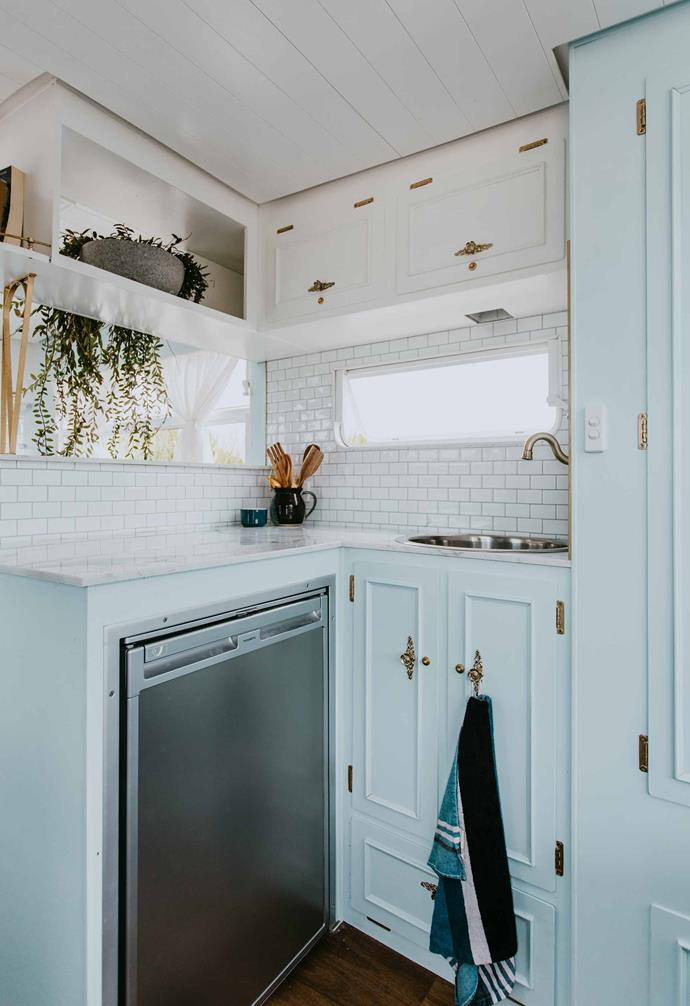 """The subway tiles elongate the compact kitchen space in [Dolly](https://www.homestolove.com.au/michael-carlene-caravan-renovation-dolly-19684