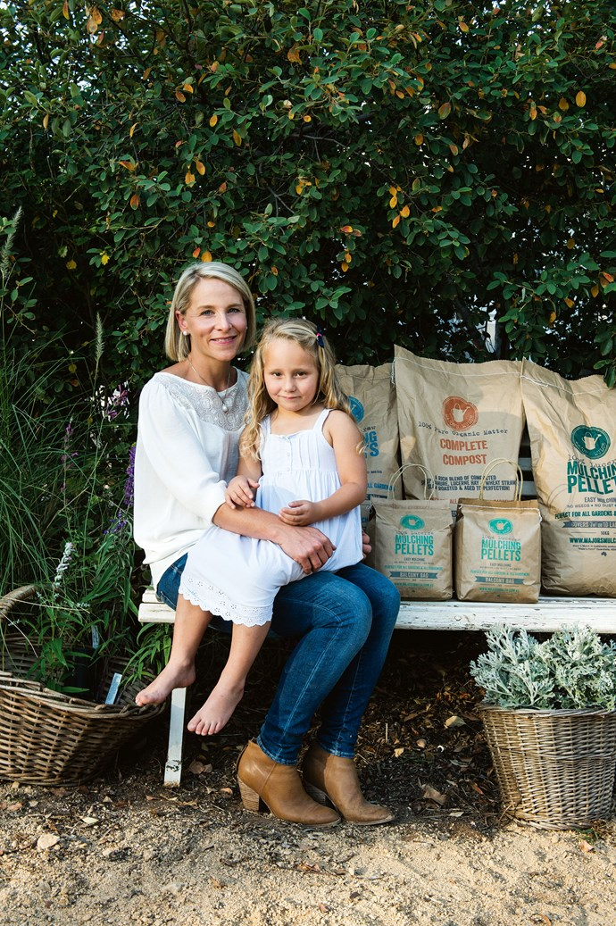 Mum and daughter next to a range of Major's Mulch products. All of the products are packaged in recyclable bags.