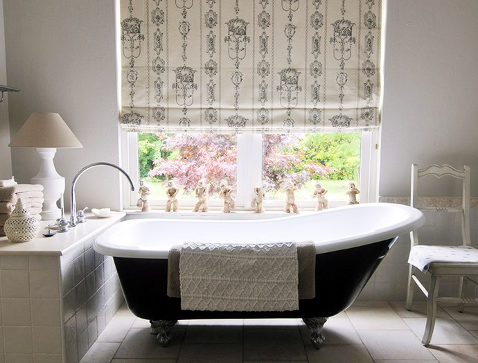 Keeping within the style of this country cottage, roman blinds have been used to dress this large bathroom window, embellished with a period print of course. *Image: Robert Reichenfeld / bauersyndication.com.au*