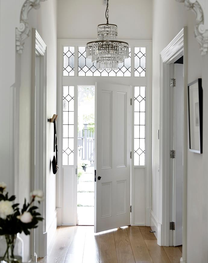 While the exterior facing is painted a bold black, the interior side of the front door is a calming white. Door and side panels custom-made by Steptoe's Renovation Supplies. Leadlight detailing by Victorian Leadlights. Chandelier from Antique Light Co. *Photograph*: Derek Swalwell | *Styling*: Heather Nette King.