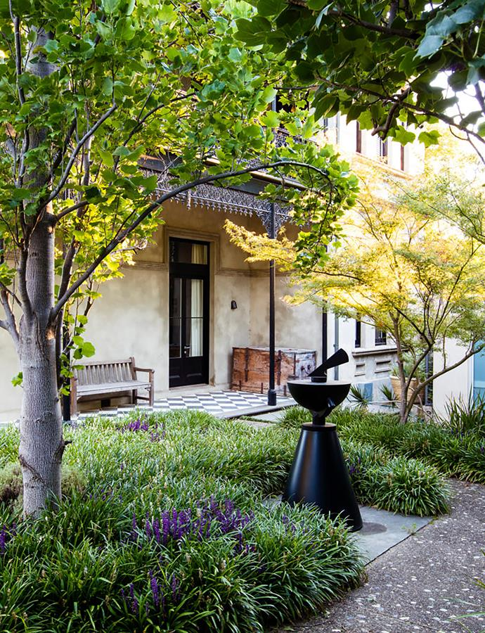 A sculptural sundial in powdercoated steel, titled Observatory by Melbourne-based artist Simon Perry, is a fitting folly in this semi-formal front garden designed by Myles Broad of Eckersley Garden Architecture. To the left is a tulip tree (Liriodendron tulipifera 'Fastigiata'), notable for its upright form and shapely leaves; to the right is a lace-leaf maple (Acer palmatum 'Dissectum Seiryu'). Mass-planted Liriope muscari in purple and white create a lush, knee-high groundcover.