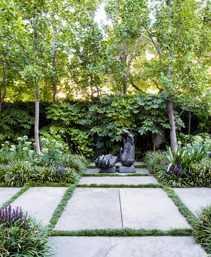 A  bronze sculpture, Chimpanzee Hands by Melbourne artist Lisa Roet, is a focal point of the front garden, where tulip trees form the tall canopy layer and lower beds contain Liriope muscari, Sedum 'Autumn Joy' and Clivia.