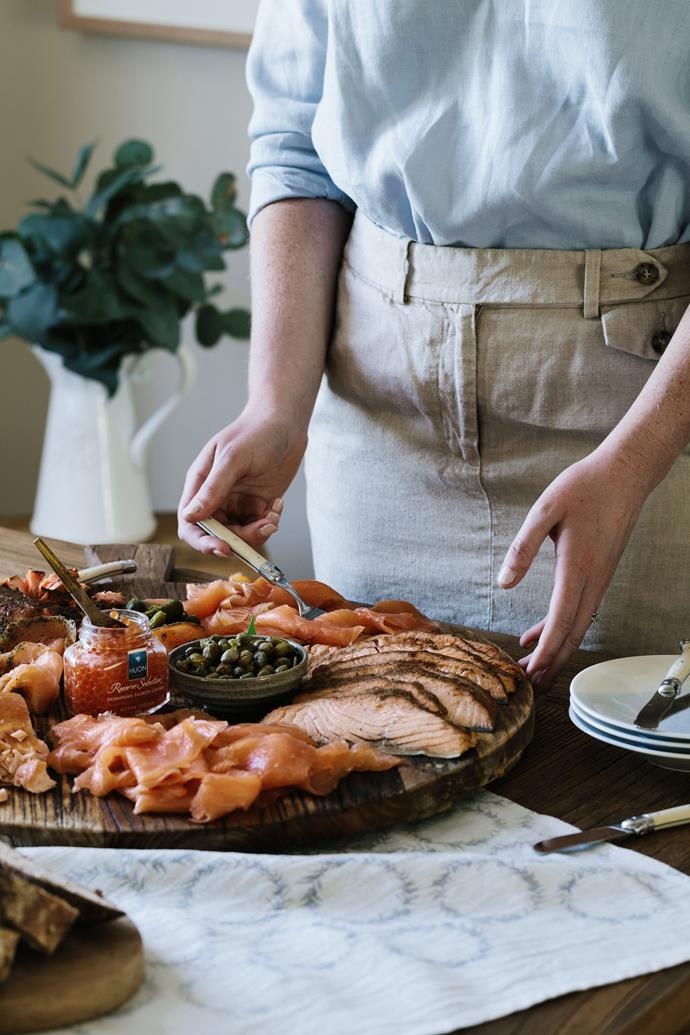 "Laura preparing a platter of family-farmed salmon. Boz also works at Huon Aquaculture as a marine farm manager. ""He worked at Huon before we got together, and then he got a lot of ribbing for going out with the boss's daughter,"" she says with a smile."