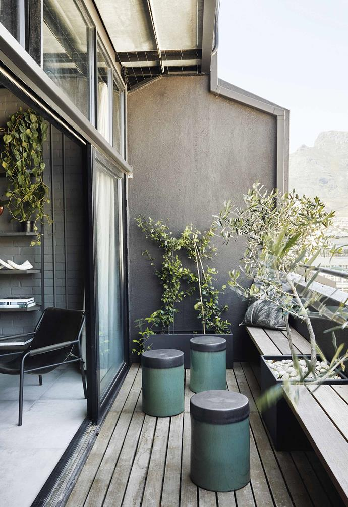 "**Balcony** ""I love sitting on the balcony with the olive trees and jasmine creeper,"" says Kim. The green stools are ceramic. Rather than crowding the balcony with a table and chairs set, built-in benches provide ample room for Kim and her guests to enjoy drinks al fresco with a front-row view of the city skyline."