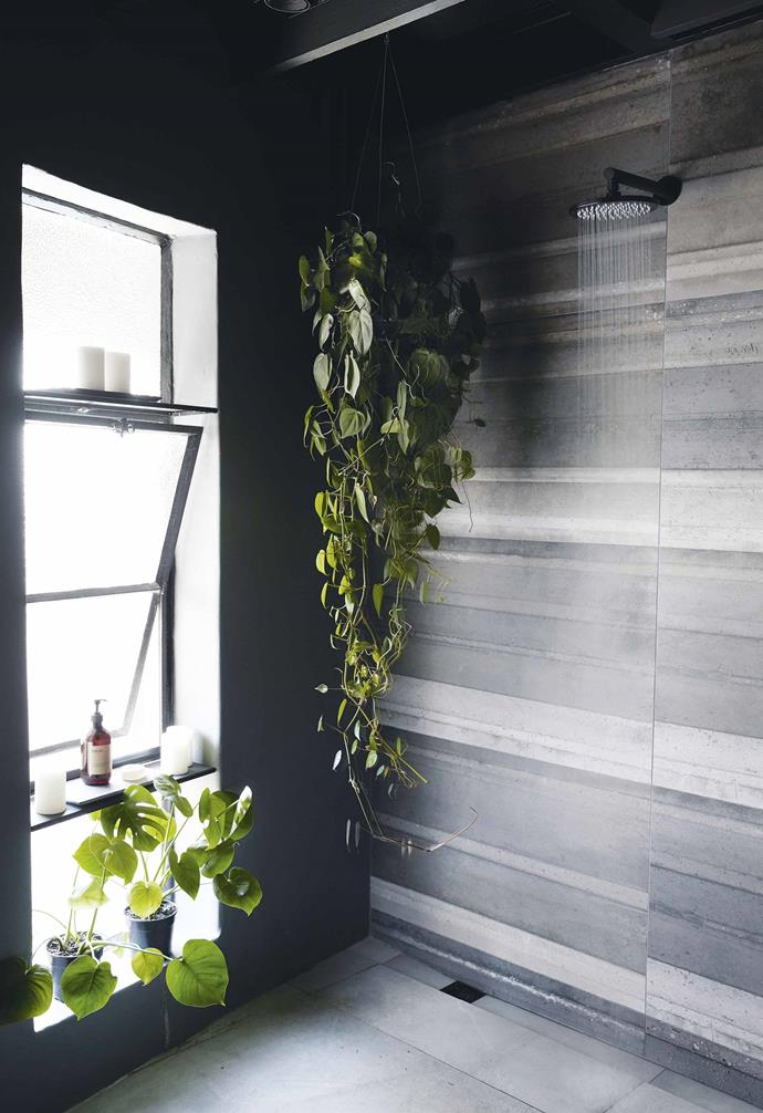 **Bathroom** The bathroom was transformed during the reno. Kim opted for a natural cement palette and had an oversized shower installed. Kim's penchant for open shelving extends to this space while the hanging plants lend a tropical feel.