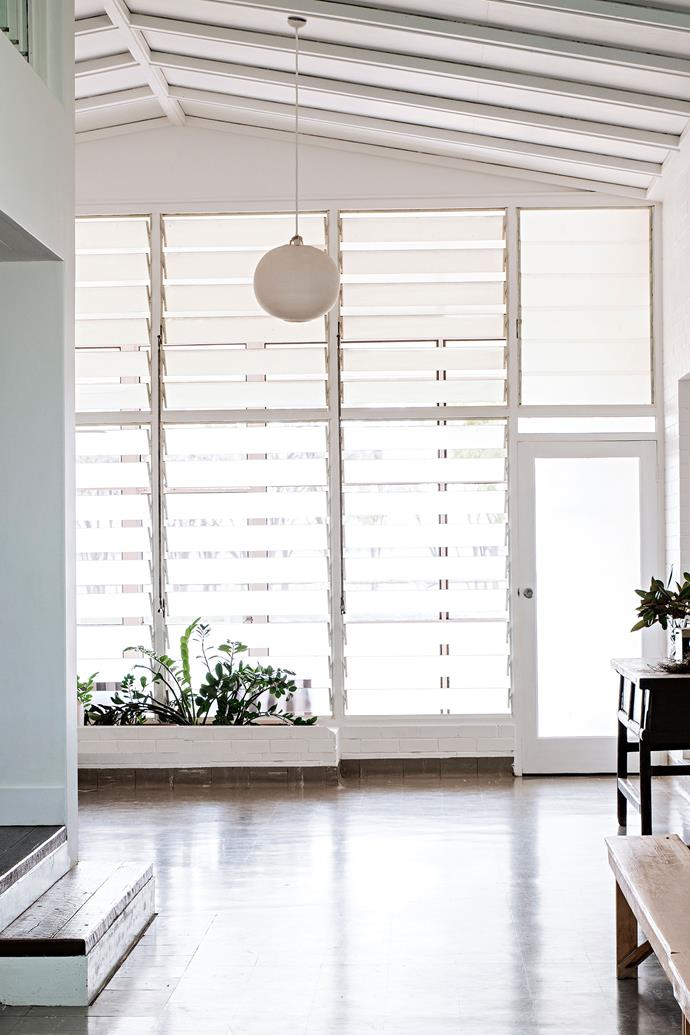 """Open living spaces under the raked ceiling are flooded with light filtering the home's [glass louvred windows](https://www.homestolove.com.au/house-window-styles-and-names-5514 target=""""_blank"""")."""