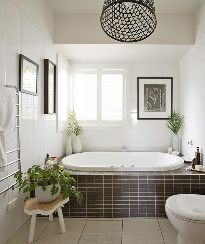 This bathroom has been brought back to life with the addition of a woven light shade, simple pot plants and stylish artwork. *Image: Emma McDonald / bauersyndication.com.au*