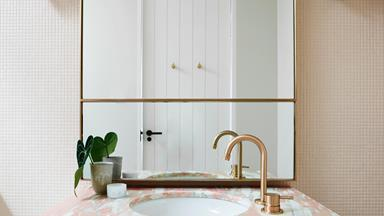 A pink children's ensuite bathroom with rose gold accents