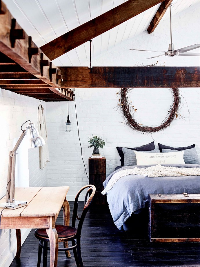 Exposed ironbark mortice-and-tenon beams feature in the main bedroom. The hanging light is from Tomolly.