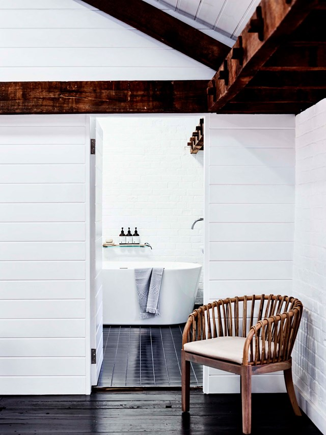 """A modern bath juxtaposes against exposed timber beams and wall panelling in this [old flour mill](https://www.homestolove.com.au/flour-mill-home-conversion-19095