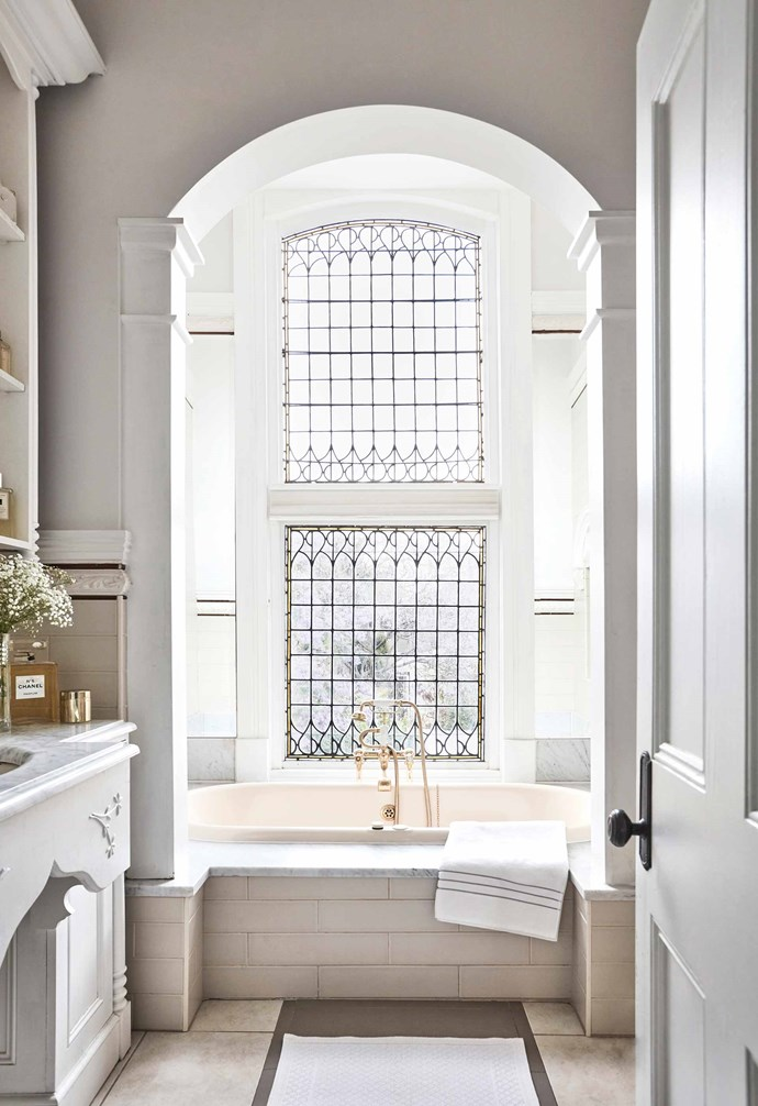 **Bathroom** The dramatic embellished windows over the bathtub flood the bathroom with natural light.