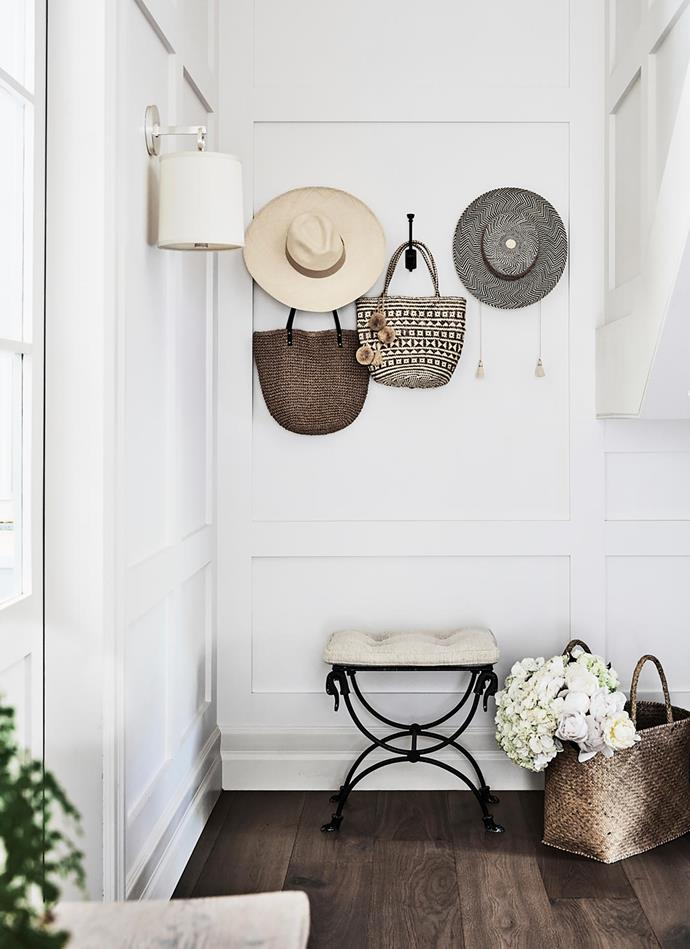 A charming nook beneath the stairs. Visual Comfort & Co 'French Cuff' sconce in Soft Silver with silk shade, Laura Kincade. Antique stool from the UK. Baskets from South Africa. Andrea is launching an accessories label called Andi Stark this year; some of her hats are shown here.