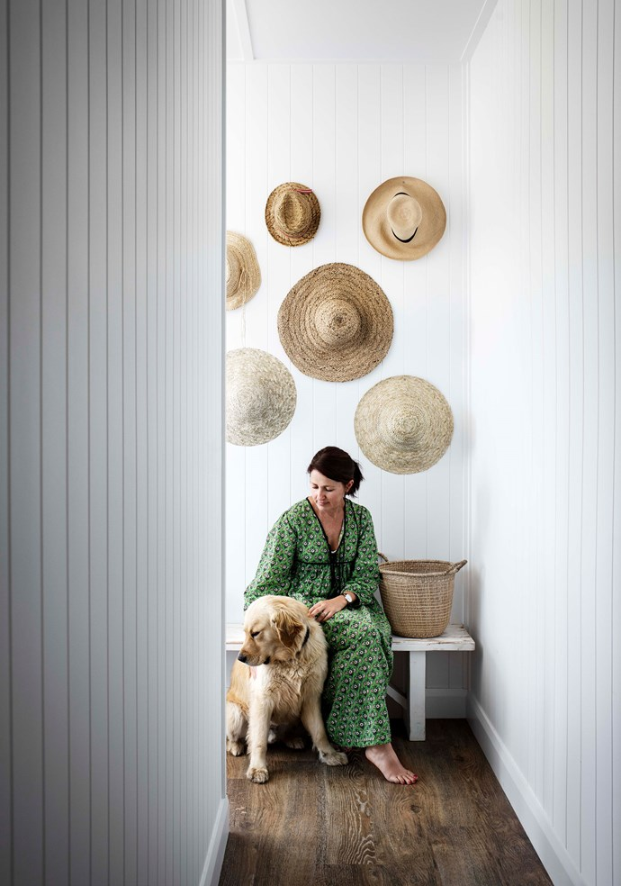 Leah with Ollie the golden retriever sitting in front of her large collection of wide-brim hats.
