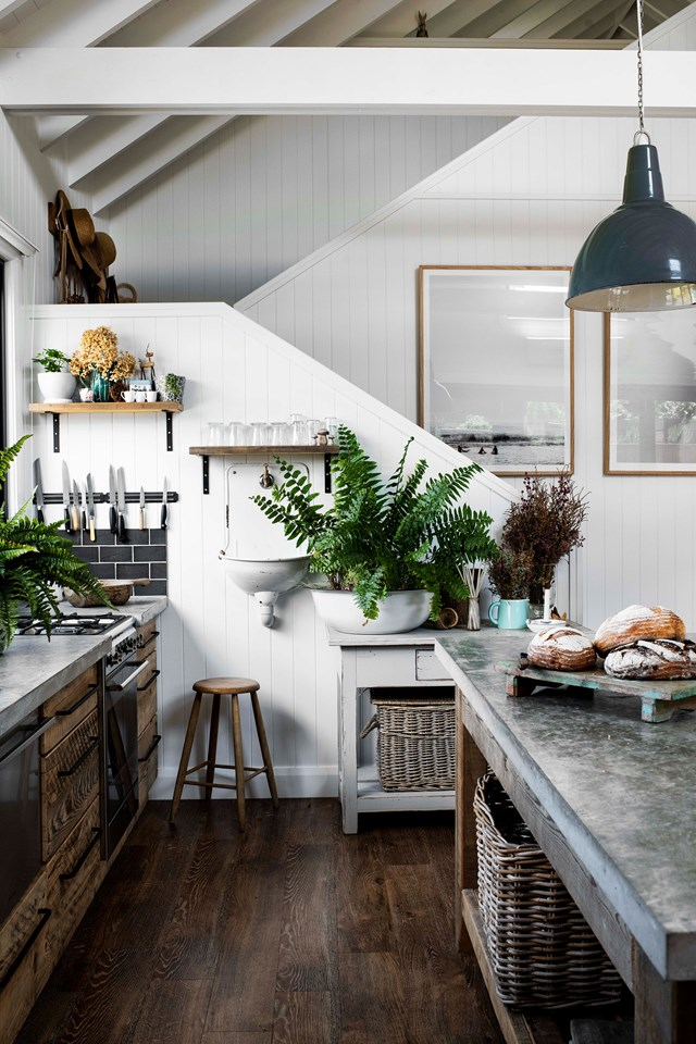 "The rustic kitchen in this [modern barn style home](https://www.homestolove.com.au/modern-barn-style-house-19961|target=""_blank"") was built from salvaged oregon and the concrete benchtops were poured on site. The lights are old factory lights and the wall-hung sink is a repurposed water fountain."