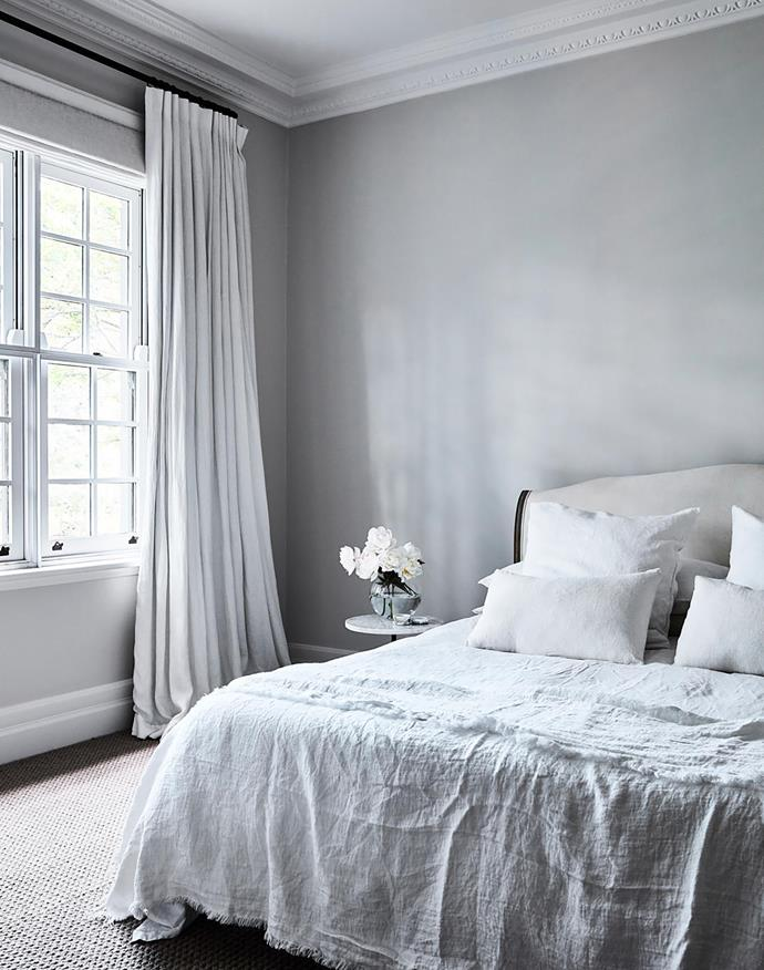"""I wanted a peaceful bedroom with warm greys, whites and snuggly soft linens,"""" says Andrea. Bedding, In Bed. Linen throw, Cultiver. Bed, Loaf (UK). Window treatments, Simple Studio. Side table, LuMu Interiors."""