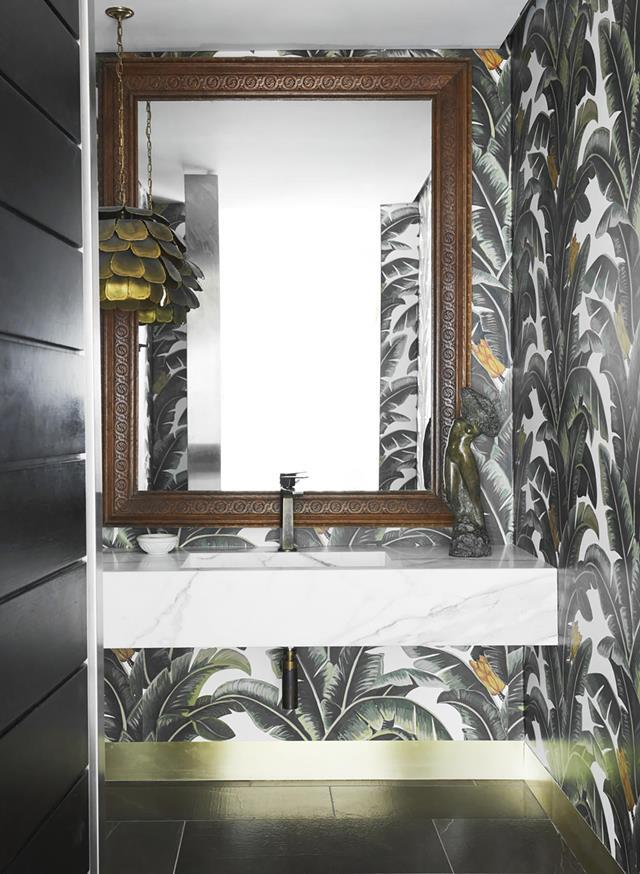 "The powder room in this [converted warehouse home](https://www.homestolove.com.au/warehouse-sydney-home-19821|target=""_blank"") echoes the tropical plantings with its leaf-motif wallpaper thanks to architect Andy Macdonald of MiArchitects. *Photograph*: Prue Ruscoe. From *Belle* April 2019."