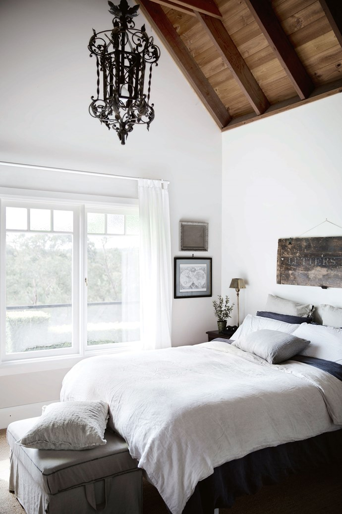 """Heidi painted the master bedroom with Dulux Antique White USA, hung simple curtains and laid sisal carpet. The rustic sign above the bed was found at [Mitchell Road Antique & Design Centre](https://www.mitchellroad.com.au/