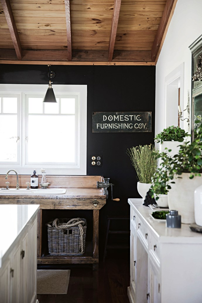 An old vice on the end of the kitchen bench reveals its former life as a workbench. It has been repurposed in this kitchen with the addition of a ceramic sink and brass tapware.