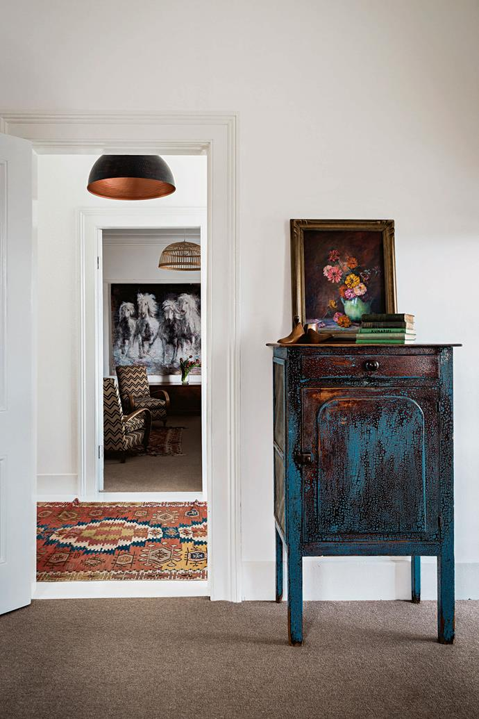 Art dominates throughout the house, including in the front two living rooms, where a bold painting of horses by local artist Gillian Jenkins and a still-life of zinnias by Florence Blake set the decorating tone. The ornate rugs  throughout the house were bought by Kate's mother on her regular trips to Turkey. The blue-painted cabinet was found at an antique store.