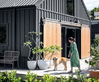 Modern barn home exterior woman golden retriever