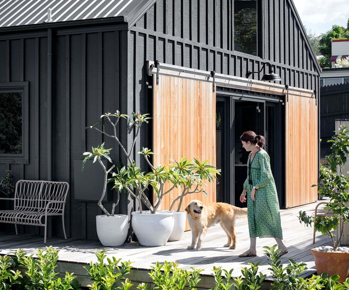 Modern barn home exterior woman golden retriever
