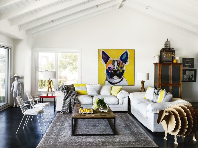 "High ceilings and painted concrete floors make the perfect showcase for Barbara's juxtaposition of bold artworks with comfortable furnishings. Plump sofas surround an antique rug, while a painting of a Boston terrier in striking hues is one of the room's main focal points. The cardboard sheep sculpture, a gift from daughter Zoe, is from [Karton Group](https://kartongroup.com.au/|target=""_blank""