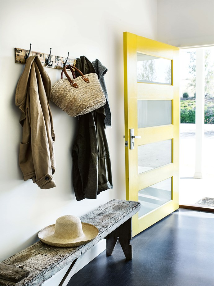 "The hallway is set off by the bold yellow [statement front door](https://www.homestolove.com.au/front-door-colour-ideas-19810|target=""_blank""), painted with Taubmans Summer Splash."