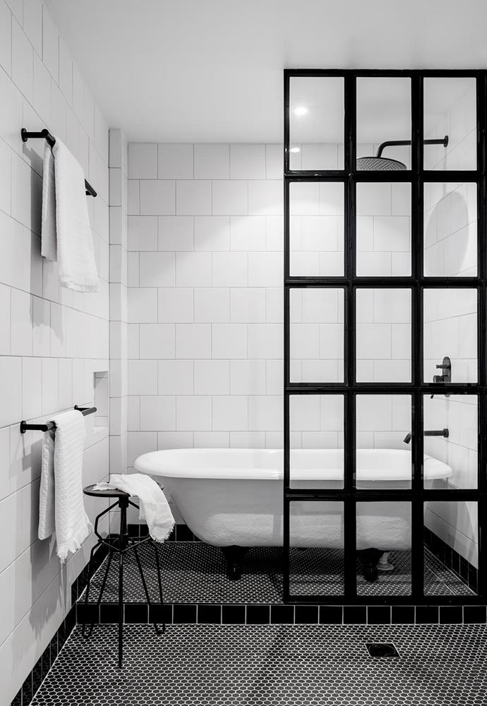 The stylish black screen creates a sense of privacy. Claw-foot bath, Traditional Bathware. Mizu 'Drift' overhead shower, arm, tap and towel rails, all Reece. Hexagonal mosaic floor tiles, Academy Tiles+Surfaces. French industrial-style stool. Smart buy: Ceramica Vogue monocottura wall tiles in Ghiaccio (white; 200x200mm), $41.90/m², and Nero (black; 100x100mm), $93.45/m², Classic Ceramics.