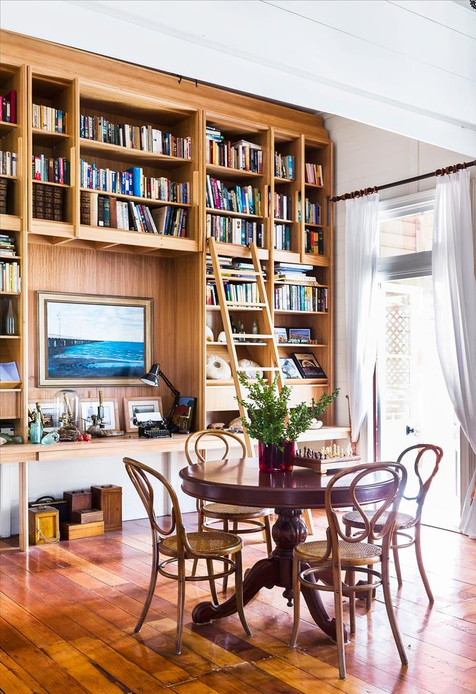 The library-style shelves, designed by Stuart Vokes and made by Desks Etc, contain all manner of books and antiques the family has collected over the years. The vintage table and Bentwood chairs are all eBay finds. Painting by Greg Dwyer. *Photograph* Maree Homer