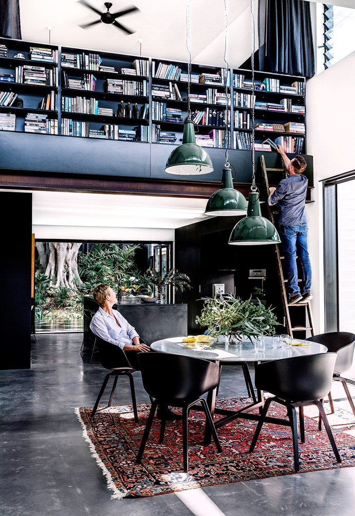 A palette of dark, moody colours and industrial materials creates a look of urban sophistication in this Brisbane home. Achieving a good spatial flow throughout the living areas was key. The elevated library is still easily accessible thanks to an antique ladder from Hobohemia. *Photograph*: Maree Homer