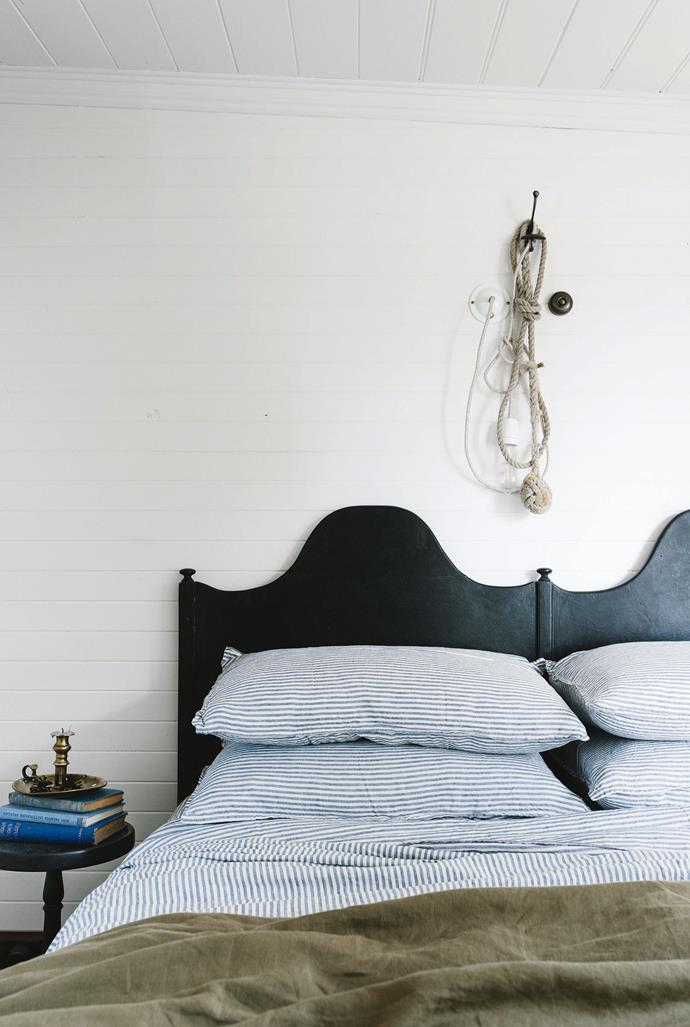 "The striped bed linen is by Bedtonic. Sarah made the eye-catching bed by cleverly joining two bedheads that were originally made for twin boys (their names are still on the back of the bedheads). The rope is a monkey's fist knot entwined with a light fitting from [Duckfat](https://duckfat.myshopify.com/|target=""_blank""), which is where Sarah sourced all the lights and light fittings."