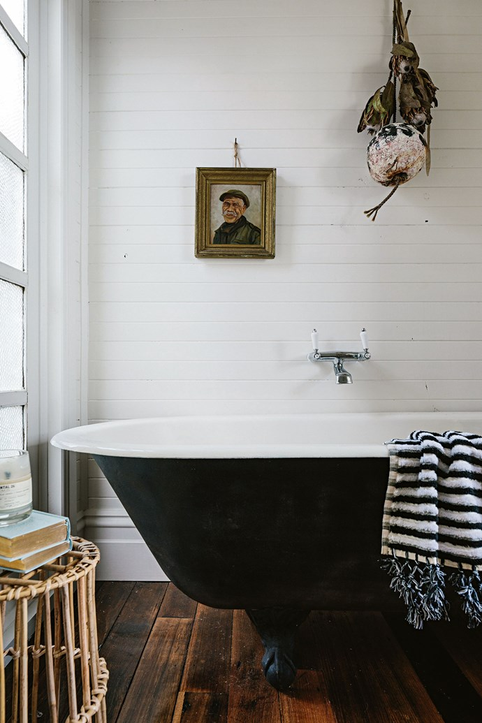 """The house is tiny, but Sarah has filled it with rustic furniture to create a comfortable space. The bedroom has a water view as does the claw-foot bath. """"It is relaxing to sit in there and soak in the view,"""" she says."""