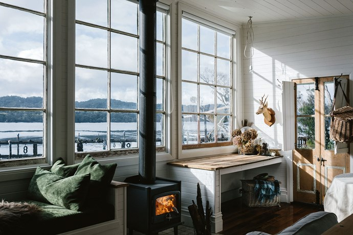 She set about sanding and polishing the Tasmanian oak floors, doing repairs, painting the internal pine lining board in Dulux Antique White USA and reinstating windows that look over the bay — where she loves to row around in her dinghy. The large, 12-pane windows were a lucky find , as they fitted the space in the old shack, the windows came from an old building in Launceston and still had the maker's name and the date '1892' on  one of the panes