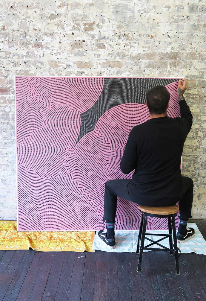 Otis Carey painting his artwork *Gaagal - Pink*, acrylic on canvas. *Photography courtesy of China Heights Gallery*.