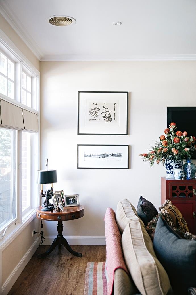 The 'Stonover Stripe' rug in the living room is Sarah's favourite. Artworks by John Olsen (top) and Peter Hickey hang above the antique side table the family brought back from the US.